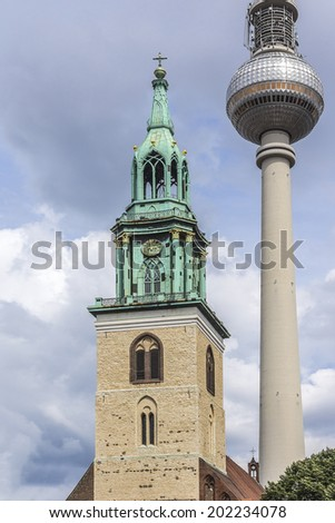 The bell tower of Marienkirche (St. Mary's Church) and the Television Tower in Alexanderplatz, Berlin, Germany. Church was built in 13th century. - stock photo