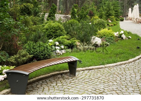 The bench on a stone path surrounded by greenery - stock photo
