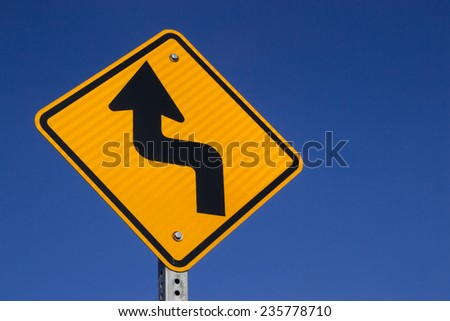 """The """"Bend in road ahead"""" sign with blue sky background. - stock photo"""
