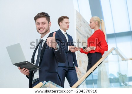 The best choice. Smiling businessman standing on a ladder and holding a laptop showing a thumbs up while his colleague businessmen talking in the background - stock photo