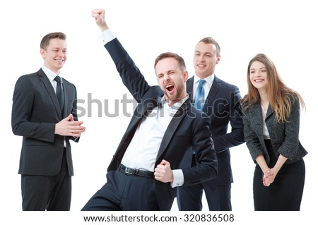 The best day ever! Business winner. Happy young bearded man in formal wear keeping arms raised and expressing positivity while his colleagues greeting him at the background. Isolated on white. - stock photo