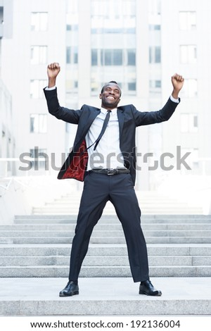 The best day ever! Full length of happy young African man in formal wear keeping arms raised and expressing positivity while standing outdoors - stock photo