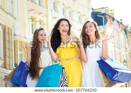 The best day to buy a dress. Three attractive young girl holding shopping bags while walking outdoors laughing and smiling - stock photo