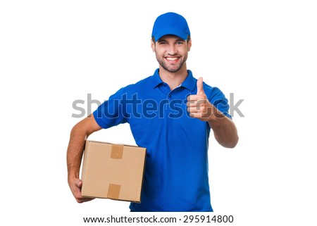 The best delivery service. Cheerful young courier holding a cardboard box and showing his thumb up while standing against white background - stock photo