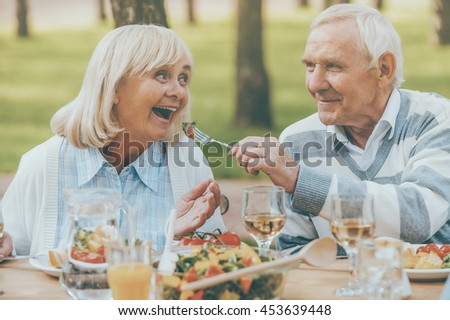 The best for our nearest. Senior man feeding his cheerful wife with fresh salad while both sitting at the dining table outdoors - stock photo