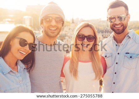 The best friends ever. Four young cheerful people bonding to each other and smiling while standing close to each other with great cityscape in the background - stock photo