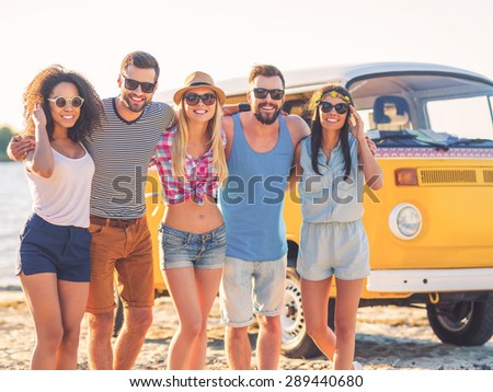 The best friends ever. Group of cheerful young people embracing and looking at camera while standing on the beach with retro minivan in the background - stock photo