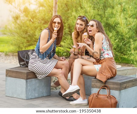 The best friends. Three beautiful woman eating ice cream in the City - stock photo