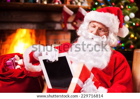The best present! Cheerful Santa Claus putting a digital tablet into the gift box and smiling while sitting at his chair with Christmas Tree in the background  - stock photo