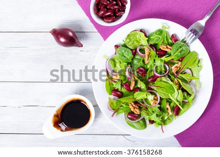 the best Red beans salad with mix of lettuce leaves and walnuts on the white dish, with caramelized balsamic vinegar in a gravy boat, Mediterranean style, with blank space left, top view - stock photo
