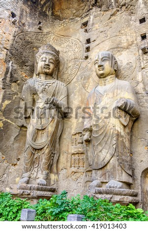 The Bhothisatta and a monk statue carved from the mountain in the Longmen Grottoes, Luoyang, China.  The picture was taken on 28th of April while touring the Longmen Grottoes that open for tourists,