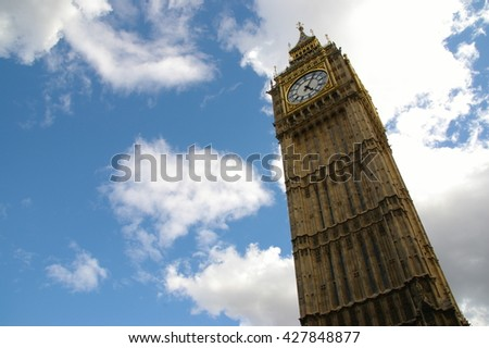 The Big Ben (in London, England, the UK) towering against the blue sky with some clouds, one July morning.