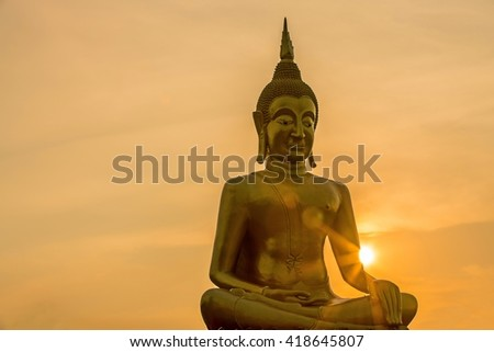 The big golden buddha statue and beautiful  twilight sky with sunset