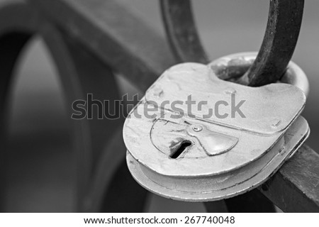 the big old iron padlock of silvery color is locked on the forged fencing, the image of the digital photo in monochrome tone - stock photo