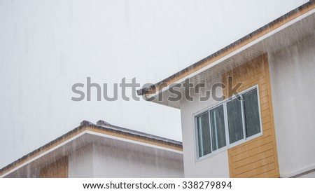 The big raining on the house roof top - stock photo