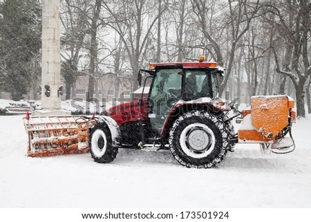 The big tractor removal snow in park - stock photo
