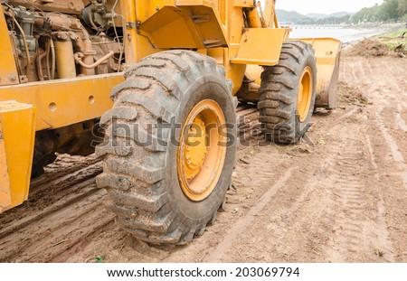 The big wheels excavator and wastes at sea beach  - stock photo
