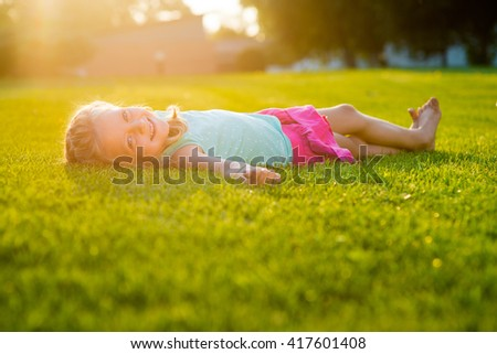 The biggest fan of nature is bathing under the Sun. The shot is full of sunlight. Green grass is everywhere.  Little lovely girl with marvelous smile. - stock photo