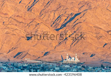 The biggest Jordanian mosque - Al-Sharif Al-Hussein Bin Ali - in Aqaba city, Jordan. Nocturnal view from the northern beach of the Red Sea in Eilat, Israel - stock photo