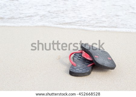 The Black and Red sandals on the beach with space for texture - stock photo
