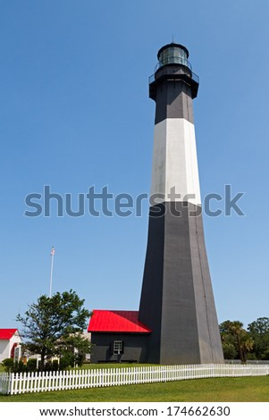 The black and white Tybee Island Lighthouse, near Savannah, Georgia, stands tall against a clear blue summer sky. - stock photo