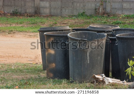 The black bins placed in the open space behind the wall. - stock photo