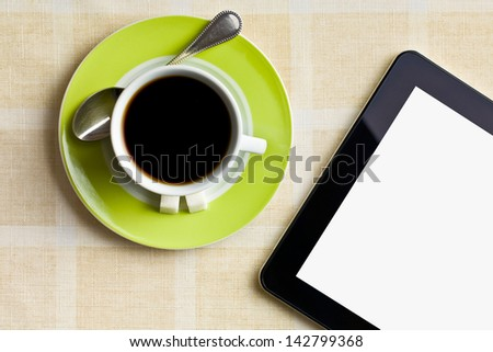 the black coffee in green cup with computer tablet