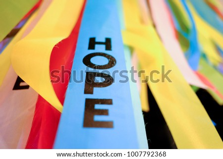 The black color of wording Hope on the multicolored fabric flag that hanging on the high board in the outdoor place at night