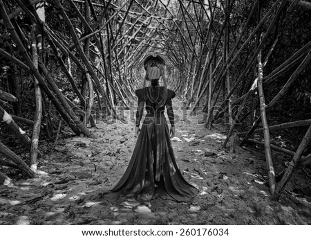 the black queen.black and white photo of the girl freak running along the corridor of the branches  - stock photo