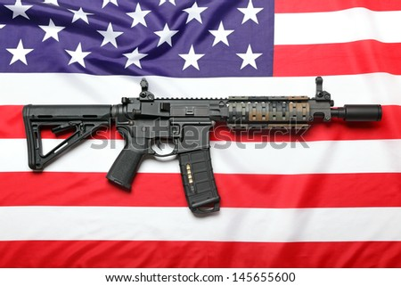 """The """"Black Rifle"""" AR-15 carbine and the flag of USA - stock photo"""