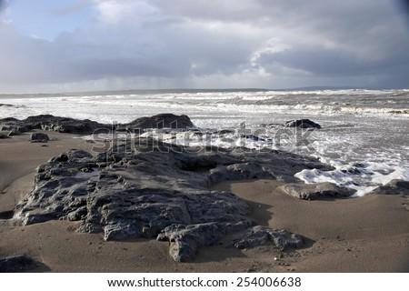the black rocks on Ballybunion beach in county Kerry Ireland after a storm - stock photo