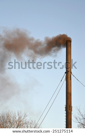 The black smoke from a pipe of a coal boiler room pollutes air. Environmental problem - stock photo