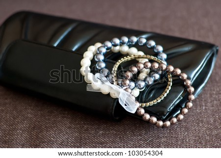 The black woman's handbag and pearl bracelets are on a brown background. - stock photo