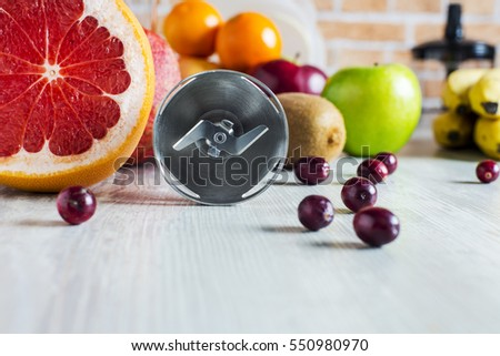 the blades of the blender on a background of variety of healthy fruits