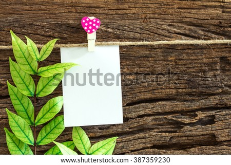 The Blank paper note hanging by red heart clips on wooden background for valentines day and love concept - stock photo