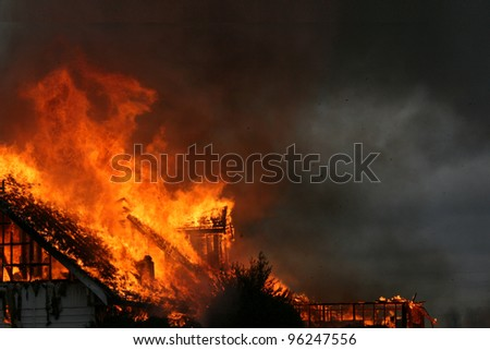 The blaze and smoke from a nighttime house fire creates an eerie dramatic photograph that could be an equally dramatic background.