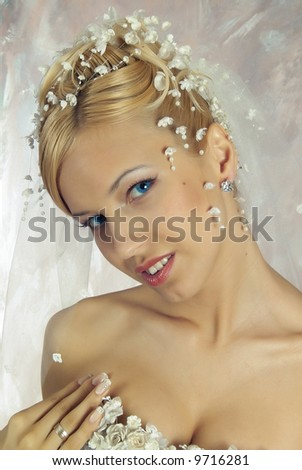 The blonde in white dress and with flower in hair. Studio photo.
