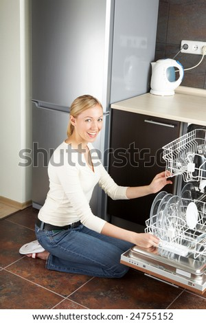 The blonde sits near to the open dishwasher on kitchen - stock photo