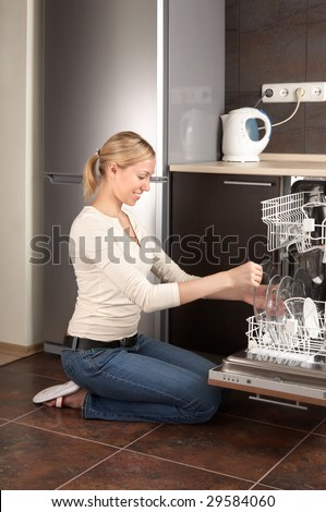 The blonde sits near to the open dishwasher on kitchen