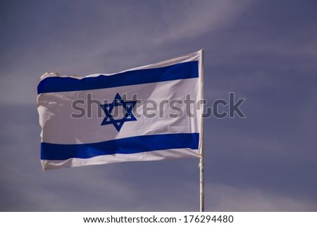 The blue and white national flag of Israel blowing in the wind.