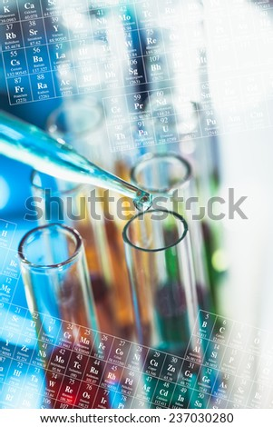 The blue drop from pipette over laboratory tubes and periodic table background - stock photo