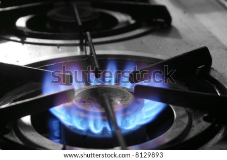 The blue flames of a gas powered stove top symbolize energy used for household purposes - stock photo