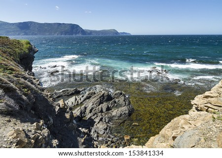 The blue-green waters of the Gulf of St. Lawrence off the cliffs of Lobster Cove Head in Gros Morne National Park, Newfoundland - stock photo