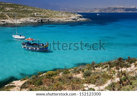The Blue Lagoon on the tiny island of Comino with Gozo in the distance. Malta - stock photo