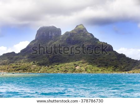 The blue sea and clouds over the mount Otemanu on Bora Bora island, Polynesia. - stock photo