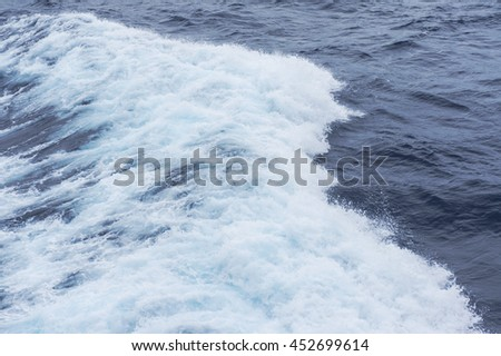 The blue sea water with spray - stock photo