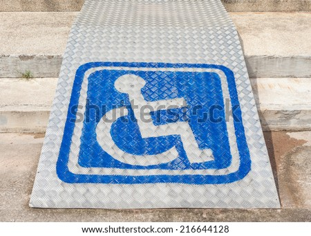The blue sign indicating on wheelchair usage on steel ramp for disabled people. - stock photo