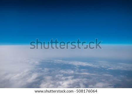 The blue sky against the background of cloud stream. View from the plane. Wide angle