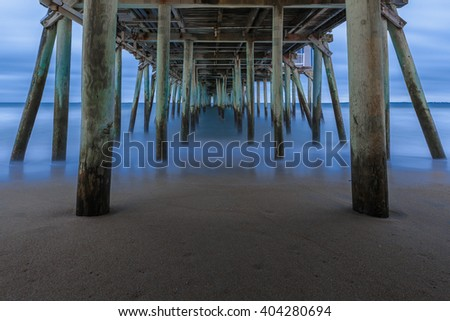 The blue waters of the Atlantic Ocean under the pier at Old Orchard Beach on a stormy morning.   - stock photo