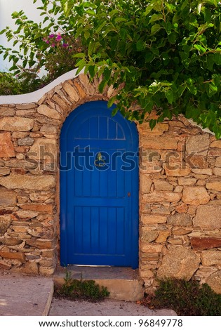 The blue wooden door on a stone wall surrounded by green bushes of the garden. - stock photo
